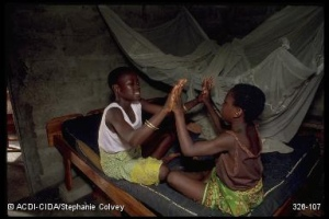 Flickr/CitizenKids:Cotonou,Bénin--Two girls sitting on a bed playing a handclapping game. The mosquito netting overhead is to protect sleepers from malaria-carrying mosquitoes